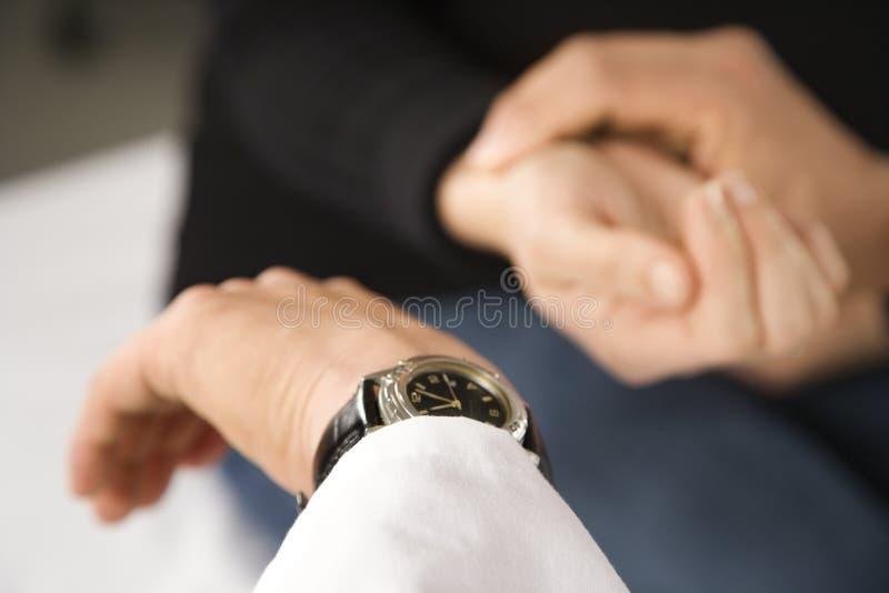 Arts die de impuls van de patiënt neemt. royalty-vrije stock afbeelding