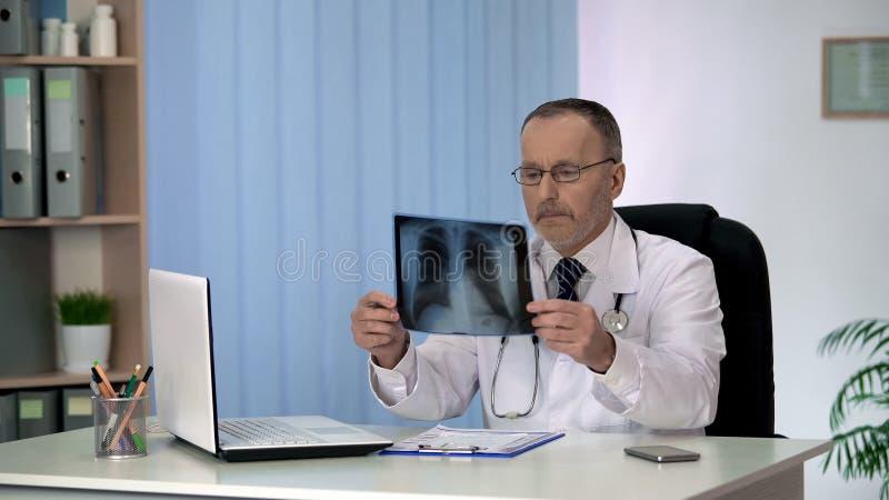 Arts die de Röntgenstraal van de patiëntenborst, de diagnostiek van de longziekte, gezondheidszorg onderzoeken royalty-vrije stock fotografie