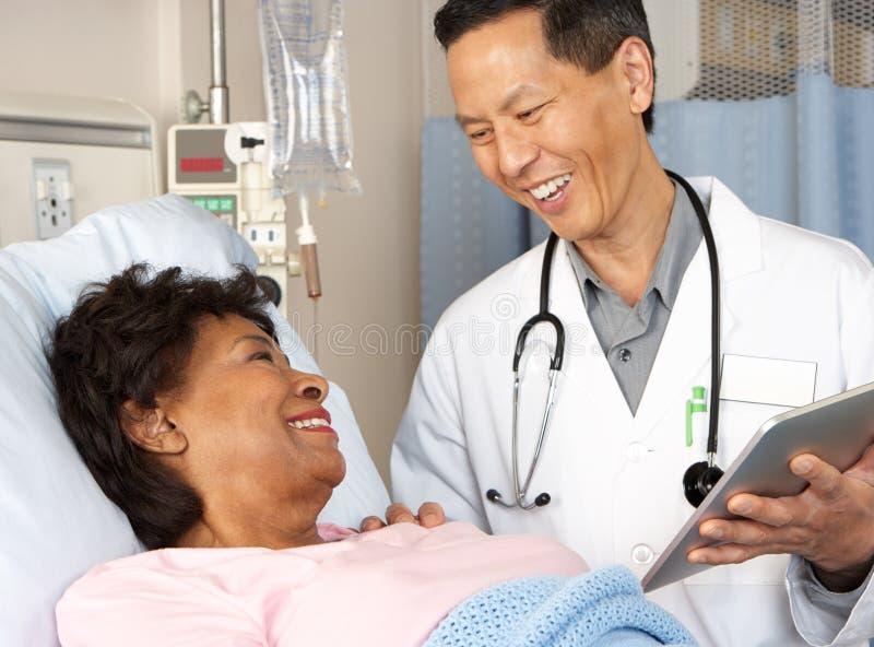 Arts die Digitale Tablet gebruiken die met Hogere Patiënt spreken stock foto