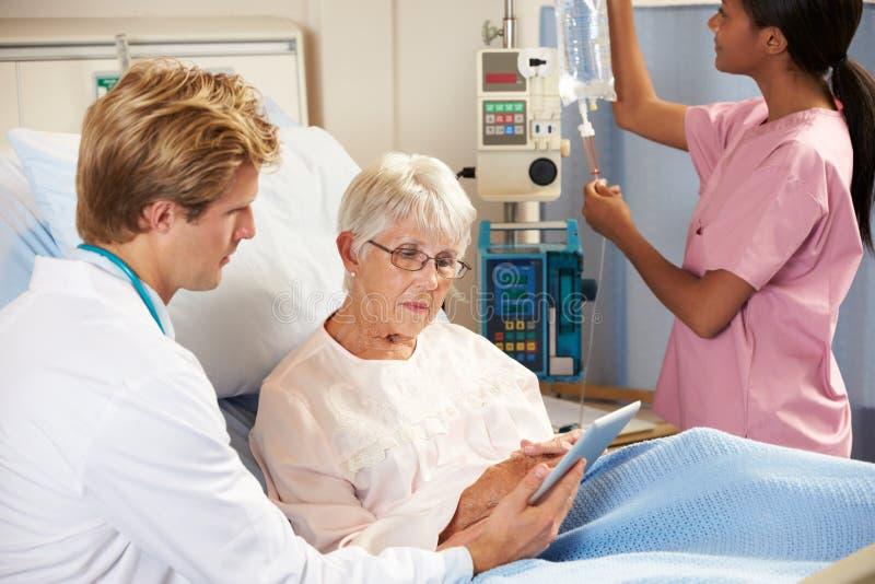 Arts die Digitale Tablet in overleg met Hogere Patiënt gebruiken stock foto's