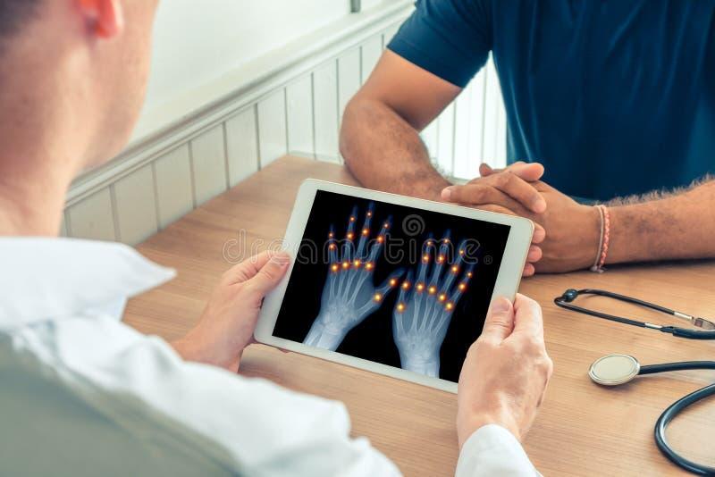 Arts die een digitale tablet met r?ntgenstraal van handen van de pati?nt houden Pijn op de verbindingen van de vingers Osteoartri royalty-vrije stock afbeeldingen