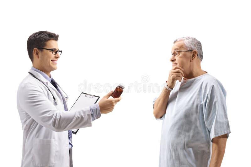 Arts die een fles van pillen geven aan een betrokken bejaarde patiënt royalty-vrije stock afbeelding