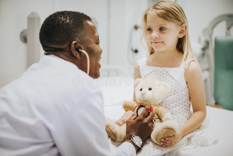 Arts die een gezondheidscontrole op een teddybeer doen stock afbeeldingen