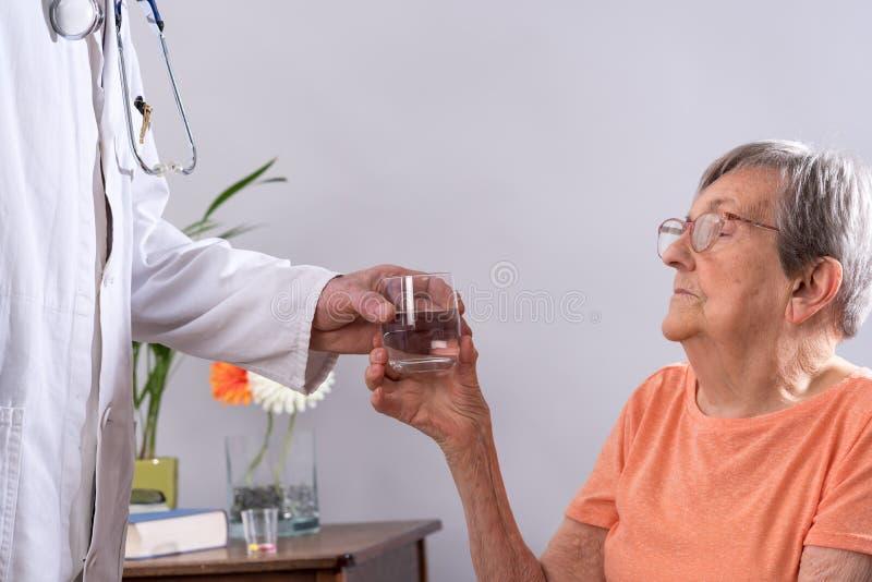 Arts die een glas water geven aan een patiënt stock foto's