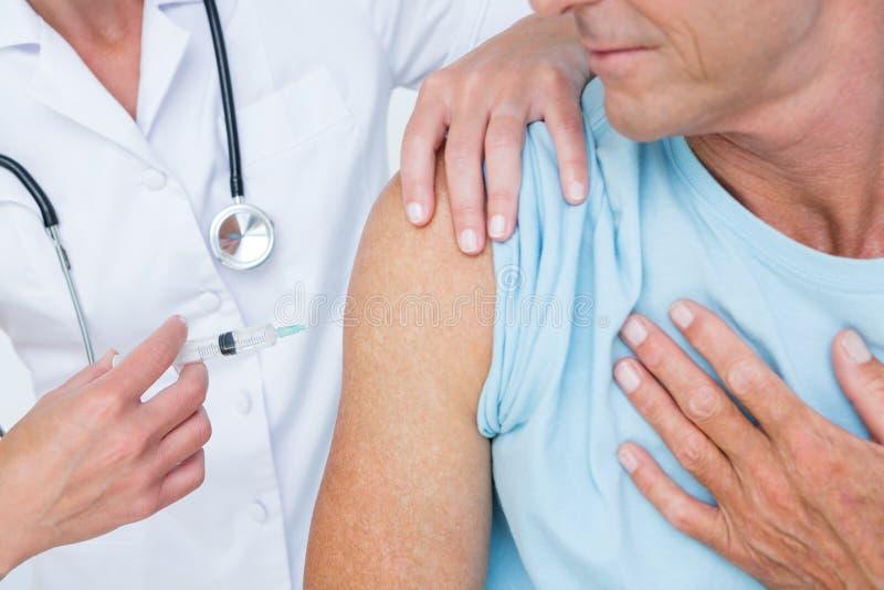 Arts die een injectie doen aan haar patiënt stock fotografie