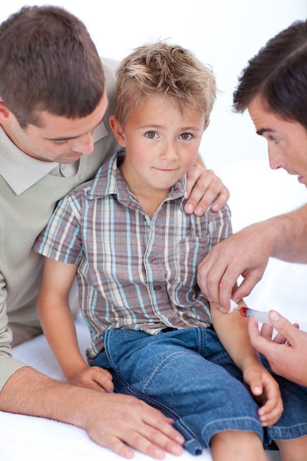 Arts die een injectie geeft aan een kind stock afbeeldingen