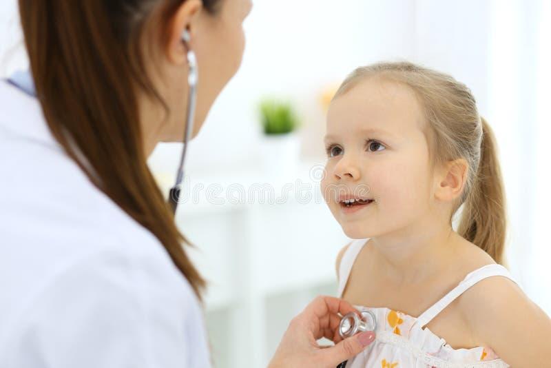 Arts die een klein meisje onderzoeken door stethoscoop Gelukkige glimlachende kindpati?nt bij gebruikelijke medische inspectie Ge stock foto