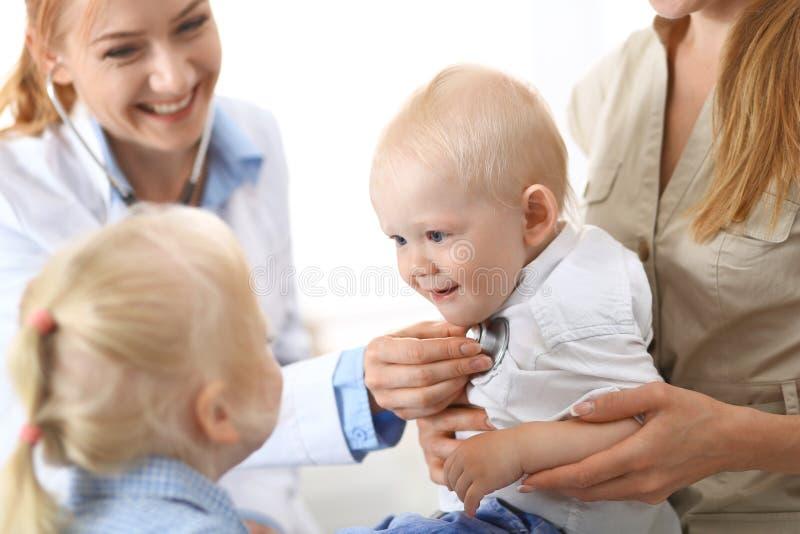 Arts die een kleine jongen met stethoscoop onderzoeken De moeder houdt haar zoon op haar overlapping Moederloos en geneeskundecon stock foto's