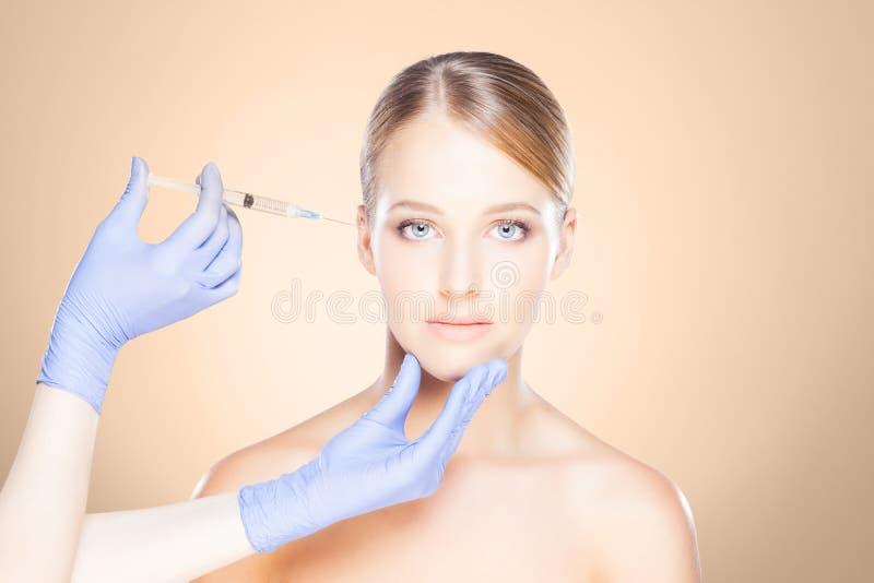 Arts die in een mooi gezicht van een jonge vrouw inspuiten Plastic s stock afbeelding