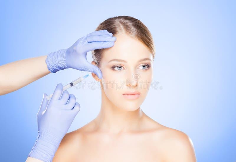 Arts die in een mooi gezicht van een jonge vrouw inspuiten Plastic s stock afbeeldingen