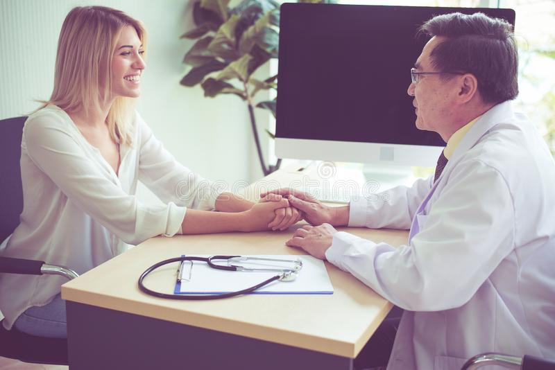 Arts die een overleg en een aanmoediging geven aan patiënt, Handenvrouw arts die haar vrouwelijke patiënt in Geestelijke het ziek stock afbeeldingen
