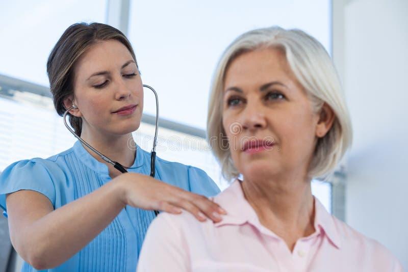 Arts die een patiënt met stethoscoop onderzoeken royalty-vrije stock fotografie