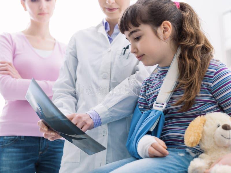 Arts die een x-ray beeld van een gebroken been tonen aan een jonge patiënt stock fotografie