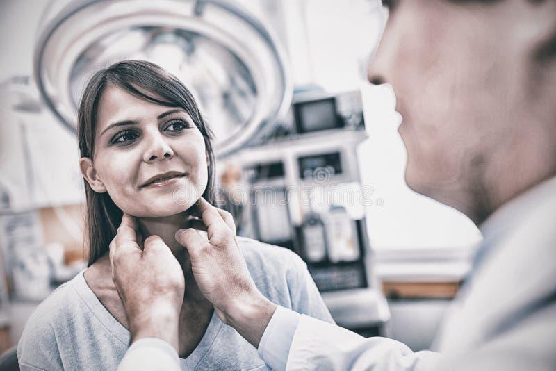 Arts die een vrouwelijke patiëntenhals onderzoeken royalty-vrije stock afbeeldingen