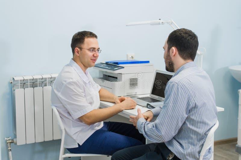 Arts die en aan patiënt in bureau glimlachen spreken stock afbeelding
