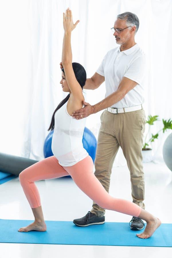 Arts die fysiotherapie geven aan zwangere vrouw royalty-vrije stock afbeeldingen
