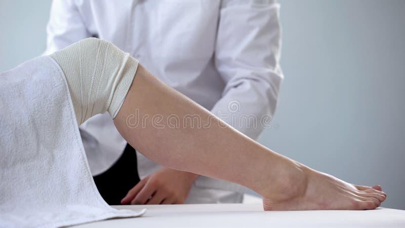 Arts die het verbonden been van de vrouw, aderlijke varices, eerste hulp voor verwondingen onderzoeken stock afbeeldingen