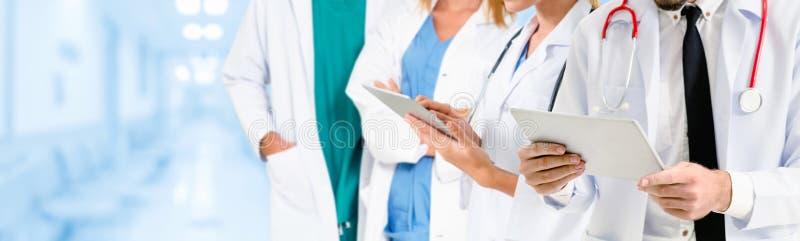 Arts die in het ziekenhuis met andere artsen werken stock fotografie