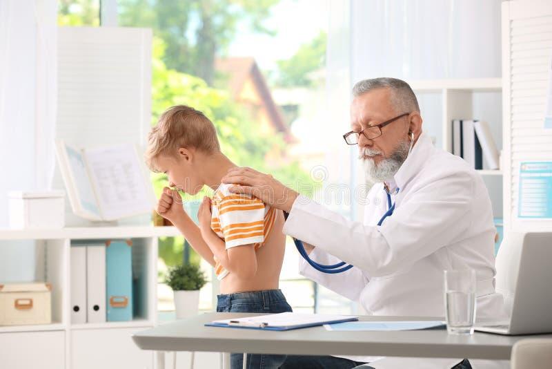 Arts die hoestend weinig jongen onderzoeken stock afbeelding