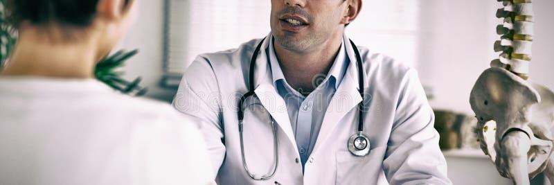 Arts die iets neerschrijven terwijl de patiënt spreekt stock afbeeldingen