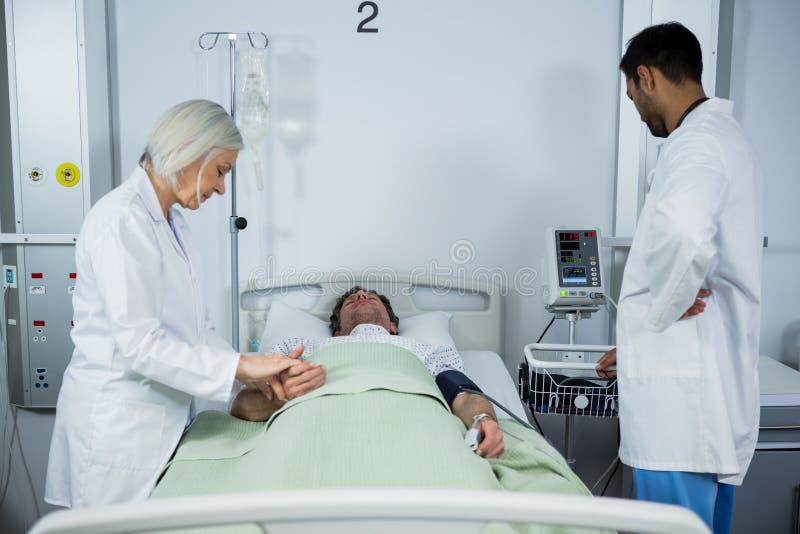 Arts die impuls van patiënt controleren royalty-vrije stock afbeelding