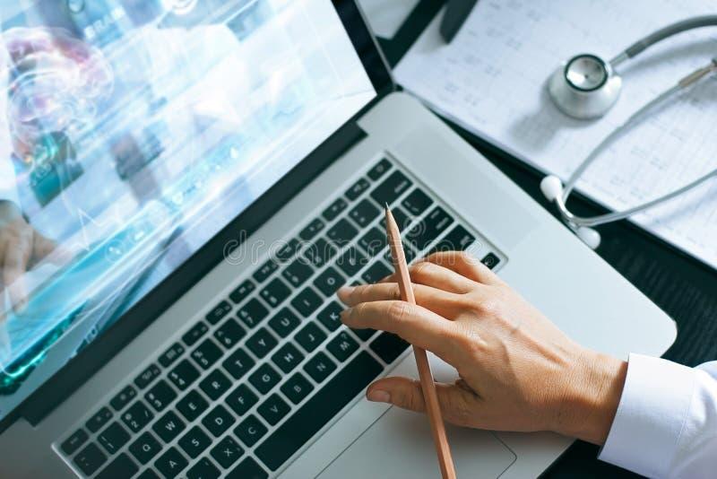 Arts die laptop met behulp van die aan het bureau met stethoscoop op gezondheidszorg werken die rapportexamen van patiënten contr stock afbeelding