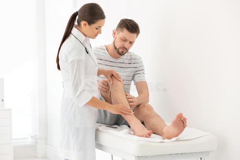 Arts die mannelijke patiënt met verwond been onderzoeken royalty-vrije stock afbeelding