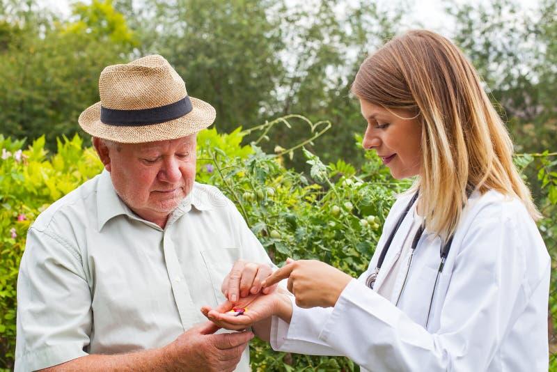 Arts die medicijn geven aan bejaarden royalty-vrije stock afbeelding