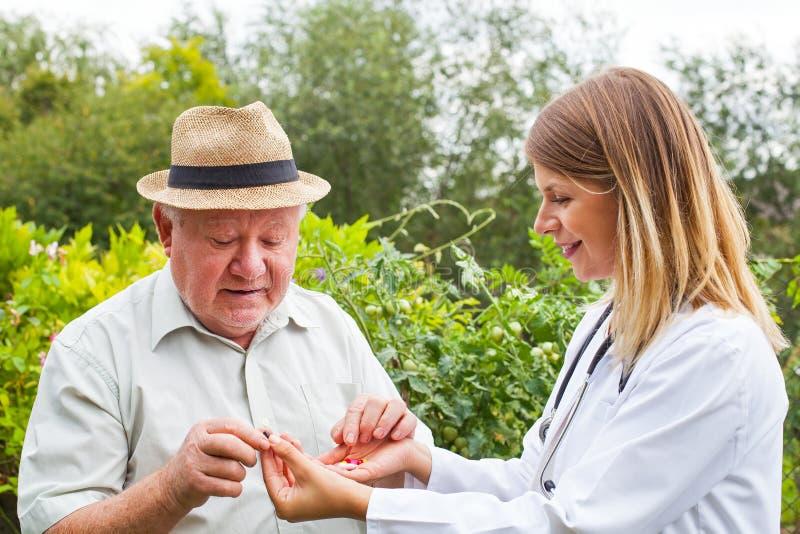 Arts die medicijn geven aan bejaarden stock fotografie