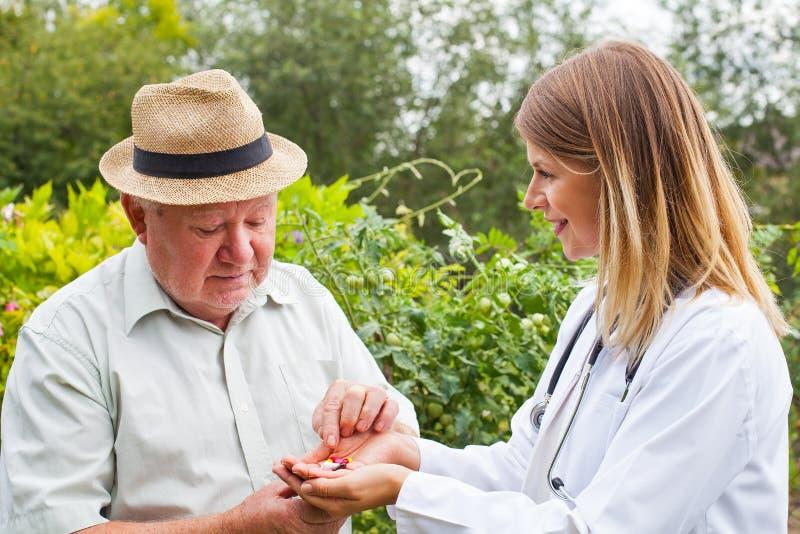 Arts die medicijn geven aan bejaarden royalty-vrije stock fotografie