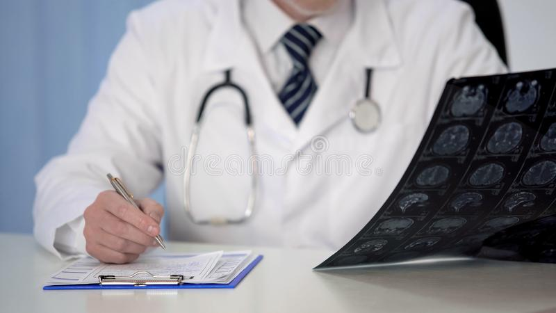 Arts die medicijn voor hersenenziekte voorschrijven, die MRI-aftasten, verzekering onderzoeken stock afbeeldingen