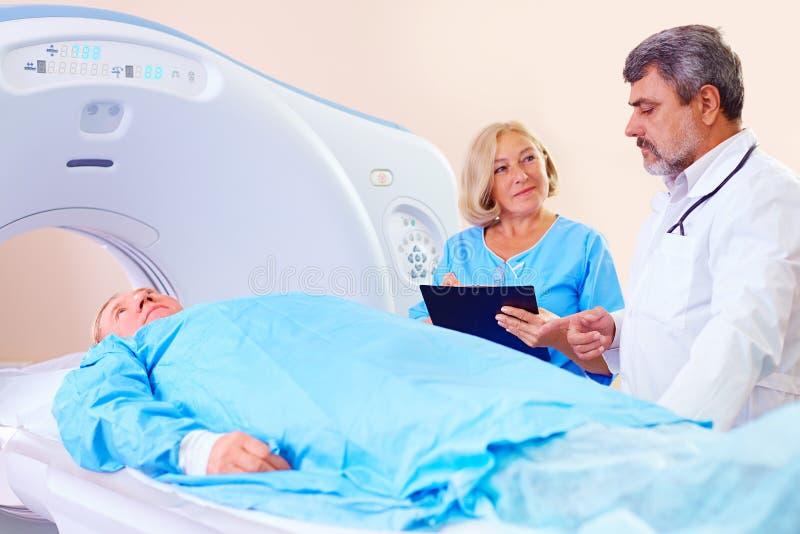 Arts die medisch personeel over CT scannerprocedure instrueert royalty-vrije stock afbeelding