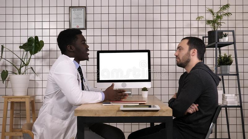 Arts die medische dossiers op zijn computer tonen aan zijn patiënt, richt hij op het scherm Witte vertoning royalty-vrije stock fotografie