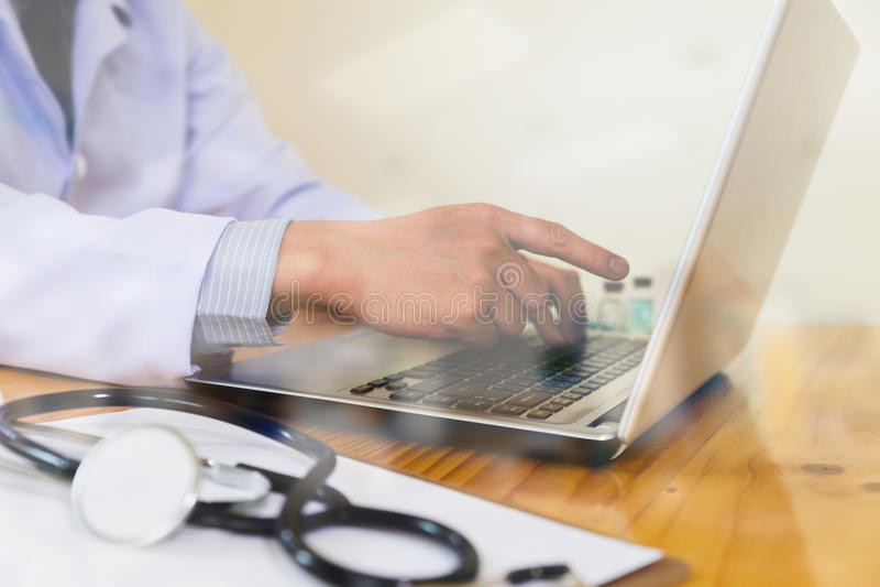 Arts die medische dossiers op zijn computer tonen, richt hij a stock afbeelding