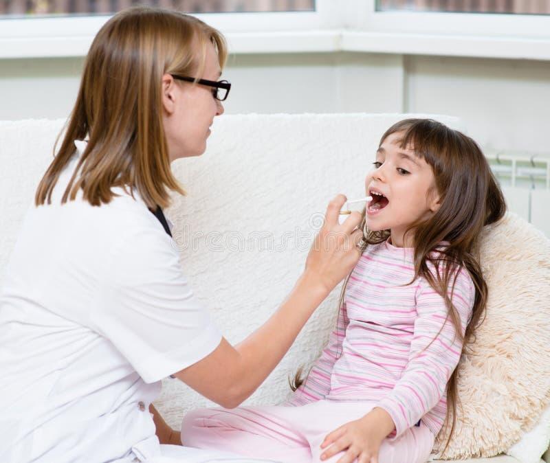 Arts die medische nevel geven aan meisje royalty-vrije stock afbeeldingen