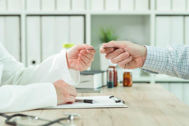 Arts die medische verzekeringskaart van pati?nt nemen stock afbeeldingen