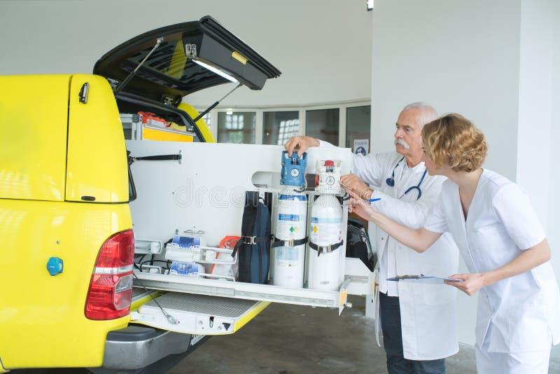 Arts die medische zuurstoftanks in ziekenwagen controleren royalty-vrije stock fotografie