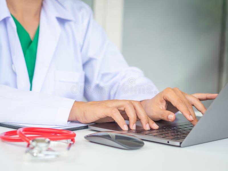 Arts die met laptop computer in haar bureau werken Gezondheidszorg A stock foto