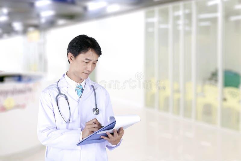 Arts die met stethoscoop op een medisch dossiergrafiek schrijven royalty-vrije stock fotografie