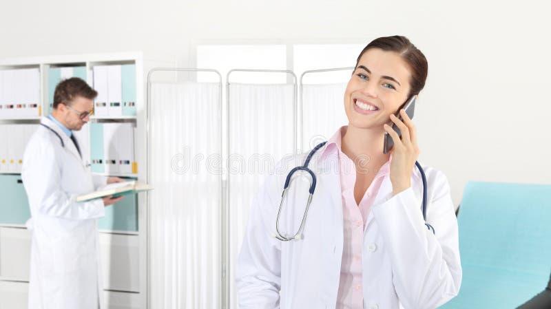 Arts die op de telefoon, concept glimlachen medische arbeider stock foto's