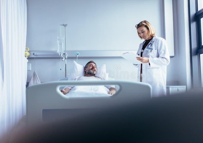 Arts die op klembord schrijven terwijl het interactie aangaan met patiënt royalty-vrije stock fotografie