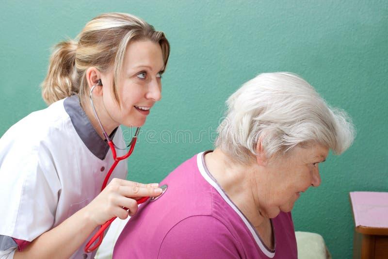 Arts die oudste met stethoscoop onderzoekt stock afbeeldingen