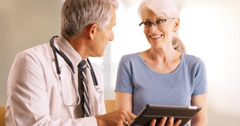 Arts die over het dossier van de bejaarde` s gezondheid in het bureau met tablet gaan royalty-vrije stock afbeeldingen