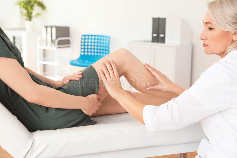 Arts die patiënt met knieproblemen onderzoeken royalty-vrije stock foto