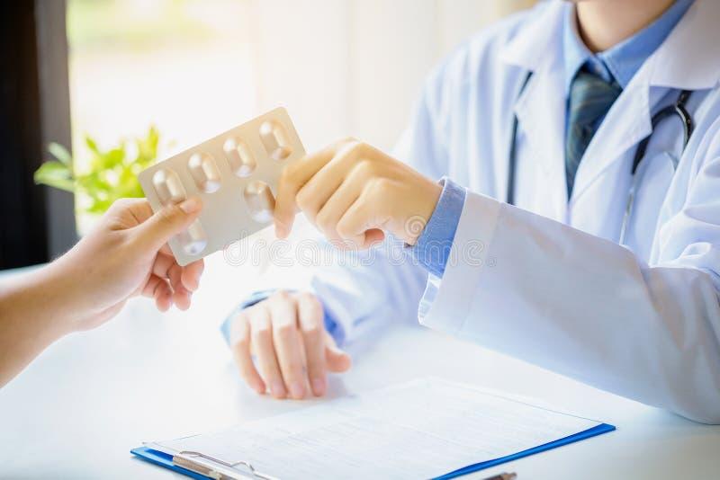 Arts die pillen geeft aan mannelijke patiënt op medisch kantoor in het ziekenhuis royalty-vrije stock afbeelding