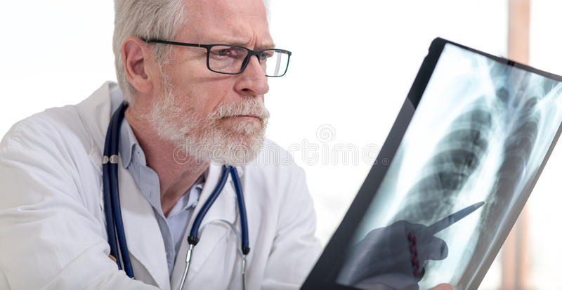 Arts die röntgenstraal bekijkt stock afbeeldingen