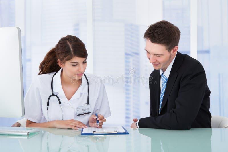 Arts die rapport tonen aan zakenman in kliniek royalty-vrije stock foto