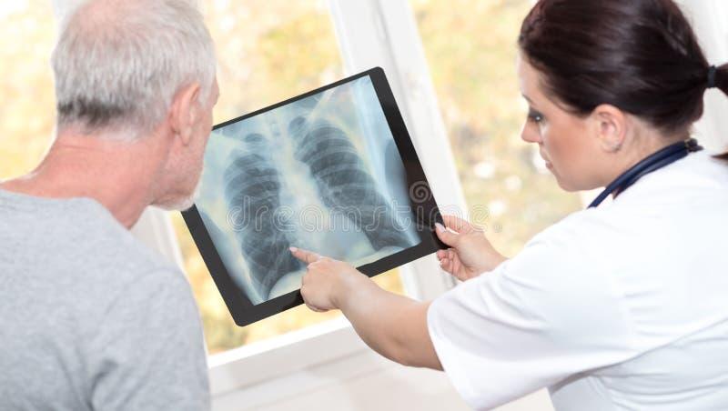 Arts die x-ray rapport tonen aan patiënt stock afbeeldingen