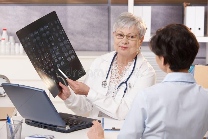 Arts die x-ray resultaten toont aan patiënt royalty-vrije stock afbeelding