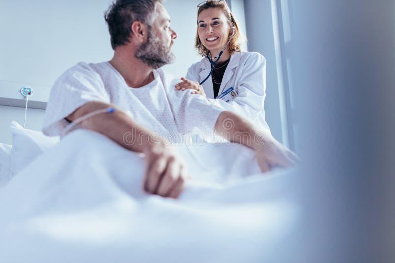 Arts die routinecontrole omhoog van in het ziekenhuis opgenomen patiënt doen stock foto's